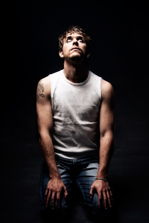 knees up: Rude man on knees looking up tattoo dark on black background