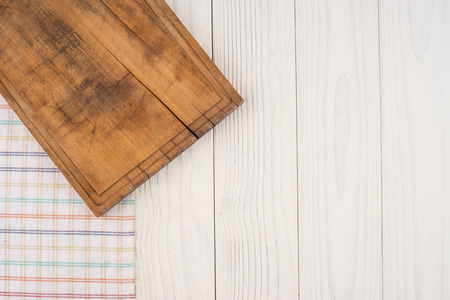 recipe background: an old cutting board in the kitchen napkin on white wooden table.Top view. Stock Photo