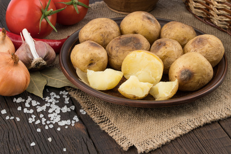 russet: baked potato in the plate on an old wooden table. Selective focus. Stock Photo