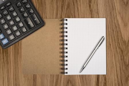 ballpen: Notebook, ballpen and calculator on wooden desk