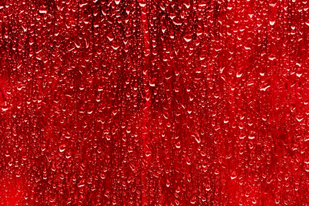 trickles: red toned drops of water on the glass.