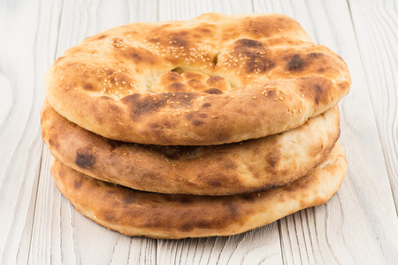 uzbek: Uzbek bread on old white wooden table. Selective focus. Stock Photo
