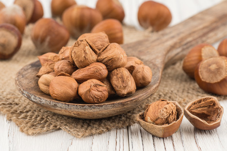 Hazelnut in wooden spoon ins old white wooden table. Selective focus. Stock Photo