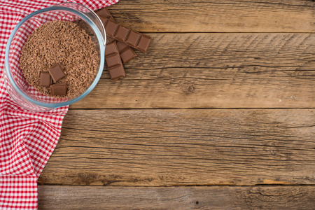 glass bowl: Grated chocolate in a glass bowl on the old wooden table. Top view. Stock Photo