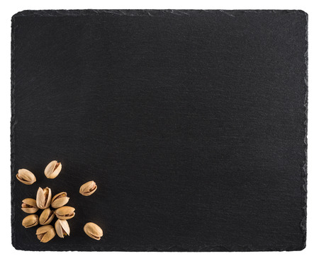 Pistachio nuts on a black slate board. Isolated on white background. Top view. Stock Photo