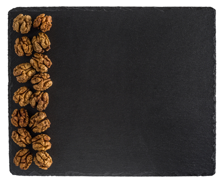 Walnut on a black slate board. Isolated on white background. Top view.