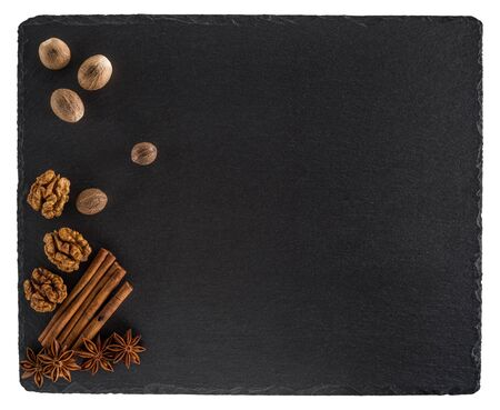 Nutmeg, walnuts, cinnamon and star anise on a black slate board.Isolated on white background. Top view.