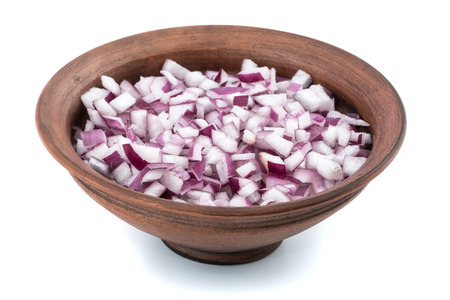 Bowl of chopped red onion on white background. Selective focus.
