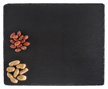 Peanuts on black slate board. Isolated on white background. Top view.