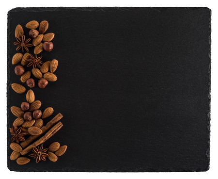 Nuts mix on a black slate board. Isolated on white background. Top view.