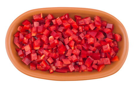 Sliced red pepper in a brown ceramic plate. Isolated on white background. Top view.
