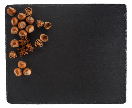 Hazelnut with anise star on a black slate board. Isolated on white background. Top view.