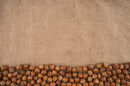 Natural, unbroken hazelnuts on a jute bag background. Top view.