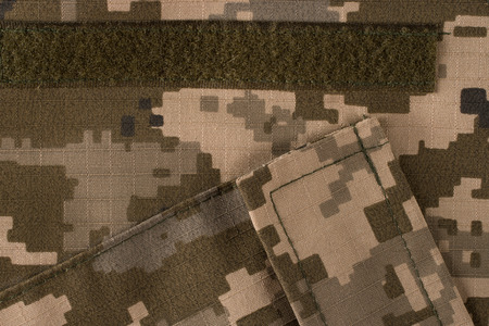 Fabric camouflage pattern with pockets. Fragment of vest. Abstract camouflage military textile background. Top view. 스톡 콘텐츠