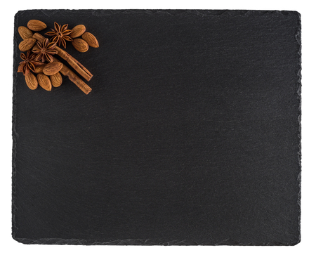 Almonds, cinnamon and star anise on a black slate board. Isolated on white background. Top view.