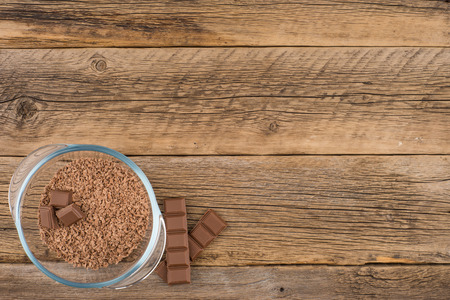 Grated chocolate in a glass bowl on the old wooden table. Top view. Stok Fotoğraf