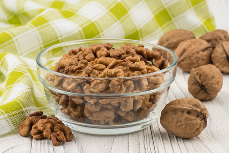 Walnuts in a glass bowl on an old white wooden table. Selective focus. Stock Photo