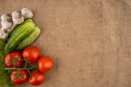 Cucumbers, tomatoes, garlic and dill on the background of old sacking. Top view.