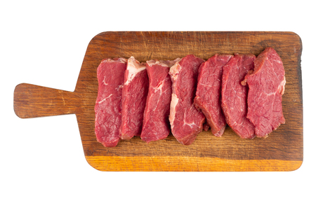 Fresh pieces of beef on a cutting board. White isolated background. top view. 版權商用圖片