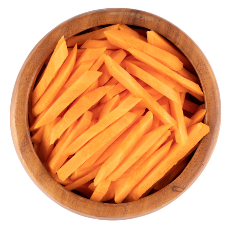 Carrot sticks in wooden bowl. Fresh cut crisp strips of Daucus carota, a root vegetable with orange color. Edible taproot pieces. Isolated macro food photo close up from above on white background. Stock Photo