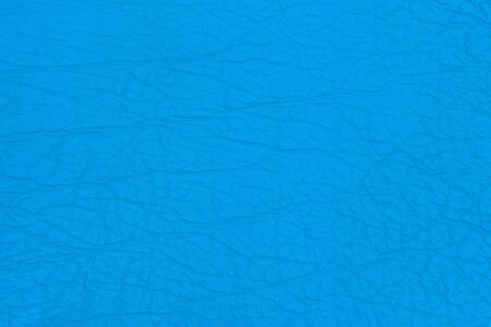 Surface faux leather with creases in blue color as background or texture. Top view.