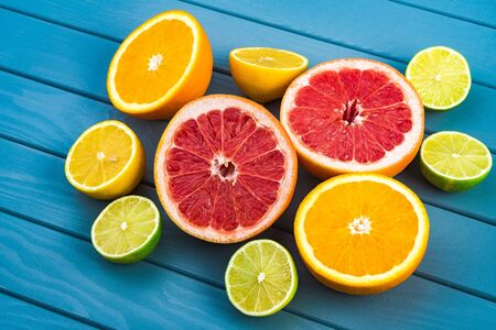 bright and juicy oranges, grapefruits, limes and lemons lie on a blue wooden table. citrus fruits, vitamins.