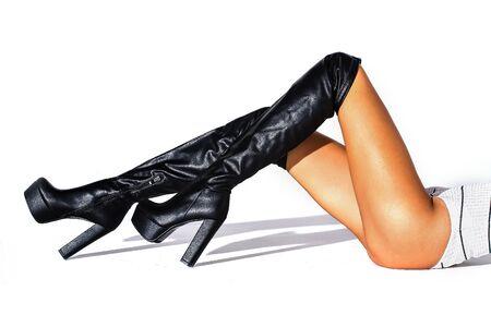 Das Mädchen liegt auf einem weißen Hintergrund. horizontaler Schuss. Schwarze hessische Stiefel an den Füßen eines Models auf weißem Hintergrund mit Schatten. Stiefeletten. Studioaufnahmen. dünne Beine. modische Stiefel. Hintergrund.