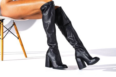 Black hessian boots on the feet of a model on a white background with shadows. jackboots. studio shooting. thin legs. fashionable boots. background