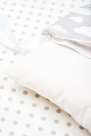 A white pillow and the cover lie on the white at the point of the sheet in the children 's roof. subject photo. soft bed.