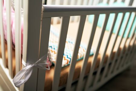 A can on white baby crib with a brown pink pillow and brown mattress. A gentle bed for the baby. subject photo Standard-Bild