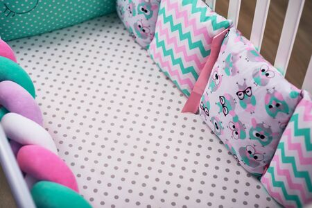 Pigtail and multicolored pillows with different patterns lie in a children 's white tree crib on a white sheet. Cozy and soft craving. subject photo