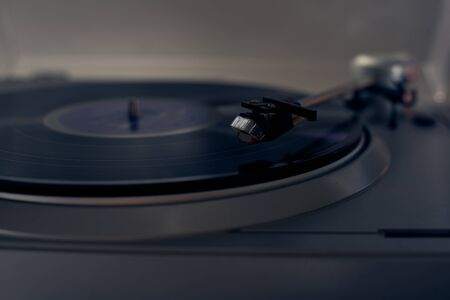 The vinyl needle reads the music from the record on a vinyl player. Old school. musical atmosphere. Old player and analog music. subject photo.
