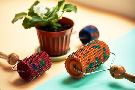Three massager with red, orange and blue drums, metallic needles lie near a vason on a yellow-green surface. Subject and promotional photography. For relaxation and health.