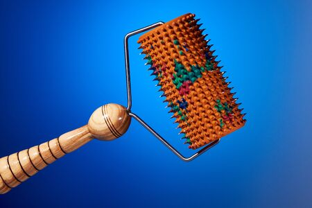 Massager with orange drum, tree handle and metal needles on blue background. is groundless. subject photo