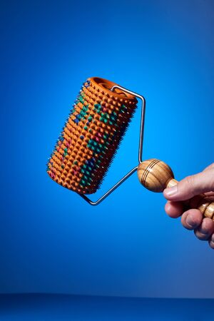 A massager with an orange drum, a plastic multicolored pen and metal needles on a blue background holds a human hand. is groundless. subject photo.