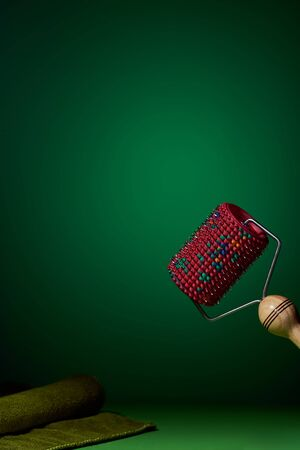 One massager with a red drum, metal needles on a green background lies near a green towel. Subject and promotional photography. For relaxation and health. Foto de archivo