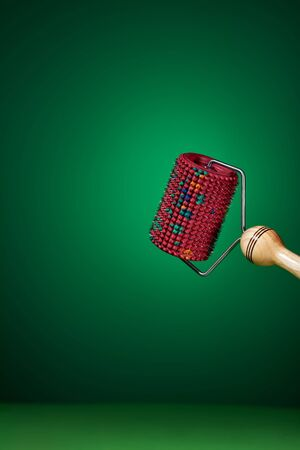 Massager with red drum, tree handle and metal needles on green background. is groundless. subject photo. For relaxation and health