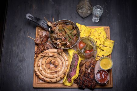 Patella, domestic sausage, meat, shashlik, kebab, salt pancakes, pickled orugs and tomatoes and sauces. food set. For the menu of cafe. wooden table. side view. macro photo. in pub.