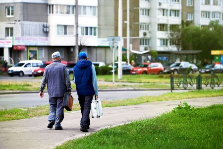 Two employees of the plumber company walk with suitcases down the street, take the road. People go to work with bags and in work uniform. Old workers.
