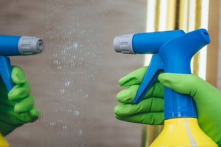 A person applies detergent to a mirror using a yellow blue cap bottle. Cleaning service of the house