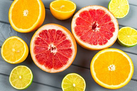 juicy oranges, grapefruits, limes and lemons lie on a grey wooden table. view from above. Lots of citrus fruit, with lots of wits and useful amino acids.