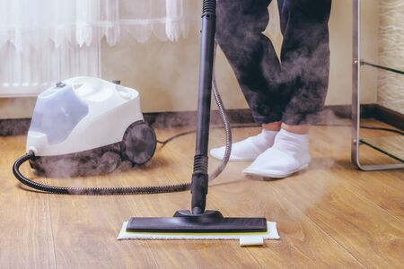 The woman washes the floor in the room with a white steam cleaner, a wet high-pressure steam. Cleaning of the apartment. we kill microbes.