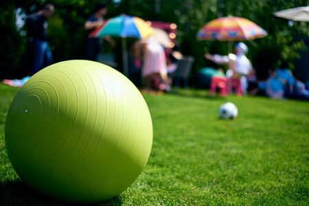 The green big rubber ball, fitball, lies on a green lawn. Children's game. Festive mood ball for fitness and aerobics.