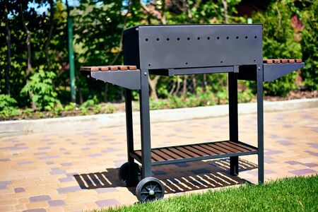 barbecue grill on wheels with wooden stands in the garden. tasty and wholesome food in the heat. future shish kebab. for holidays and events. sun