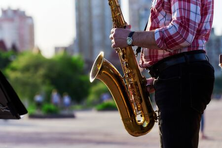 saxophonist plays a golden saxophone on the street with passers-by in sight. spring. musical reed wind instrument. tongue wooden brass musical instrument.