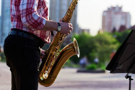 saxophonist plays a golden saxophone on the street with passers-by in sight. spring. musical reed wind instrument. tongue wooden brass instrument. Standard-Bild