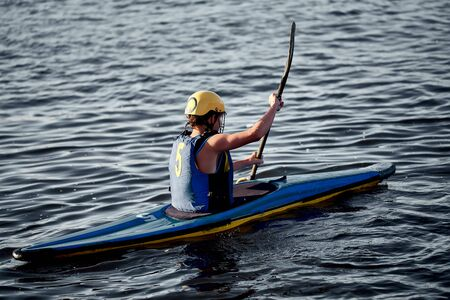 A guy wearing a helmet on a canoe polo rowing a paddle and sailing on water. canupolo. puts on a rescue yellow. rear view. Stock Photo