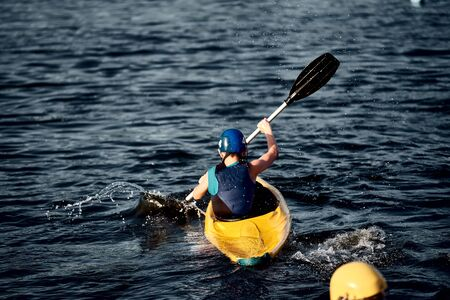 A guy wearing a helmet on a canoe polo rowing a paddle and sailing on water. canupolo. puts on a rescue yellow. water splashes.