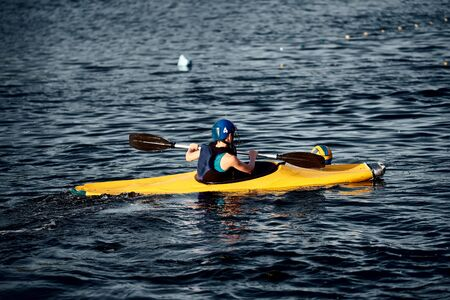 A guy wearing a helmet on a canoe polo rowing a paddle and sailing on water. canupolo. puts on a rescue yellow. rear view. water splashes Stock Photo