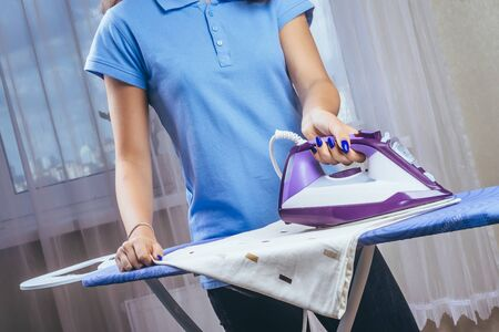 The girl holds an iron on an ironing board with a ferry and irons things. Cleaning service of the apartment. Blue T-shirt and young model. process.